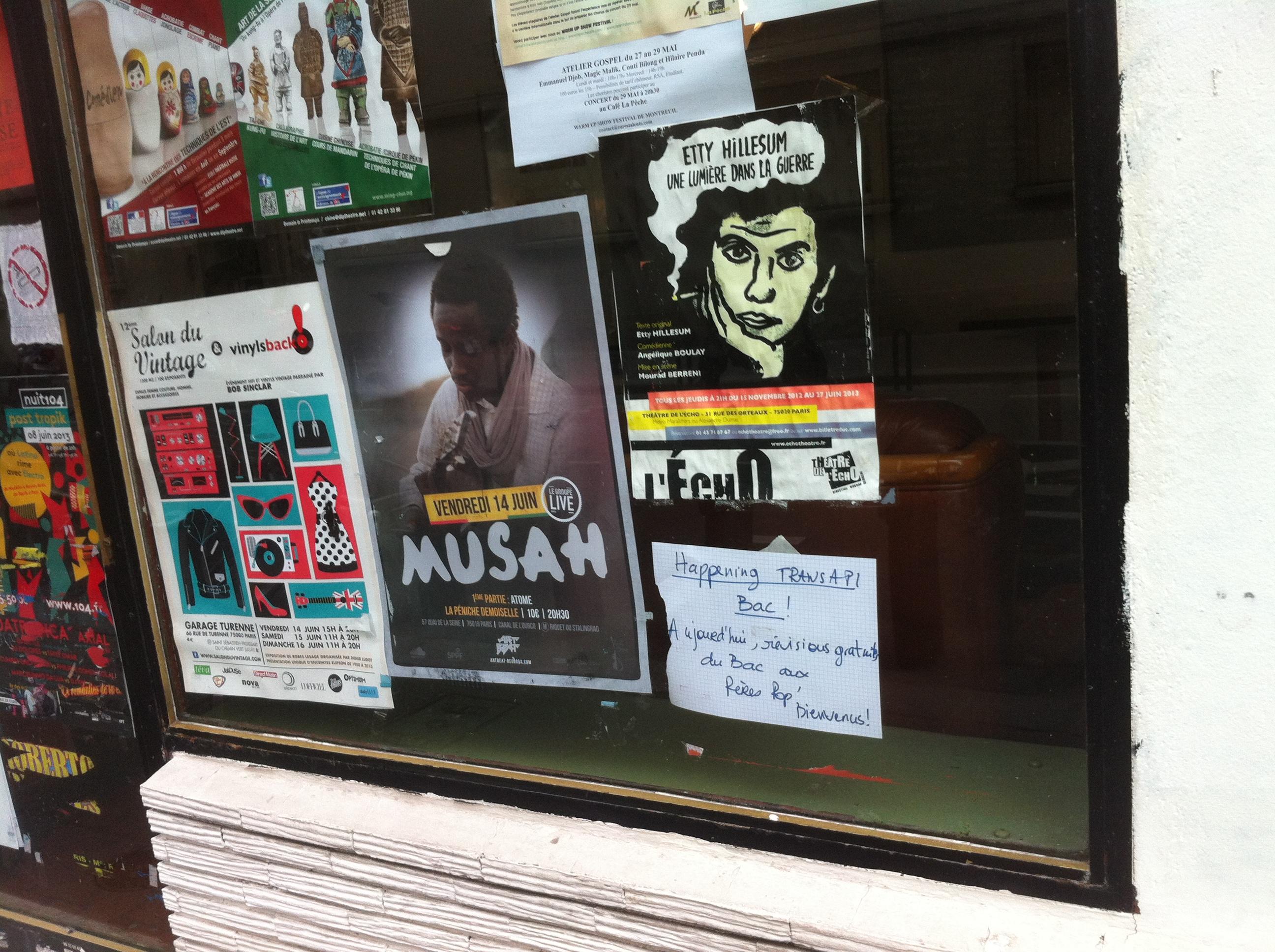 En bas à droite, une petite affiche de Transapi dans la vitrine des pères populaires